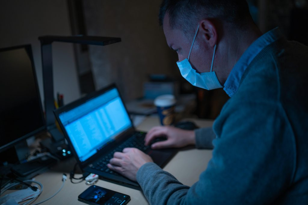 Image of man wearing surgical mask typing on a laptop computer